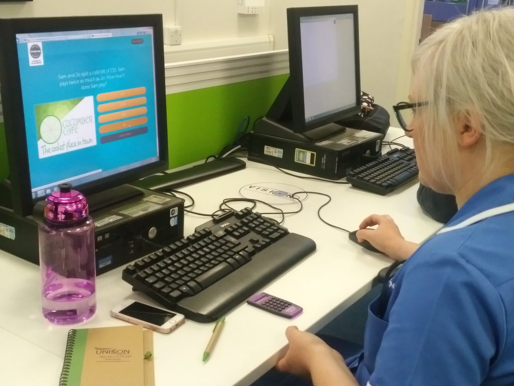 Woman looking at maths exercise on computer screen