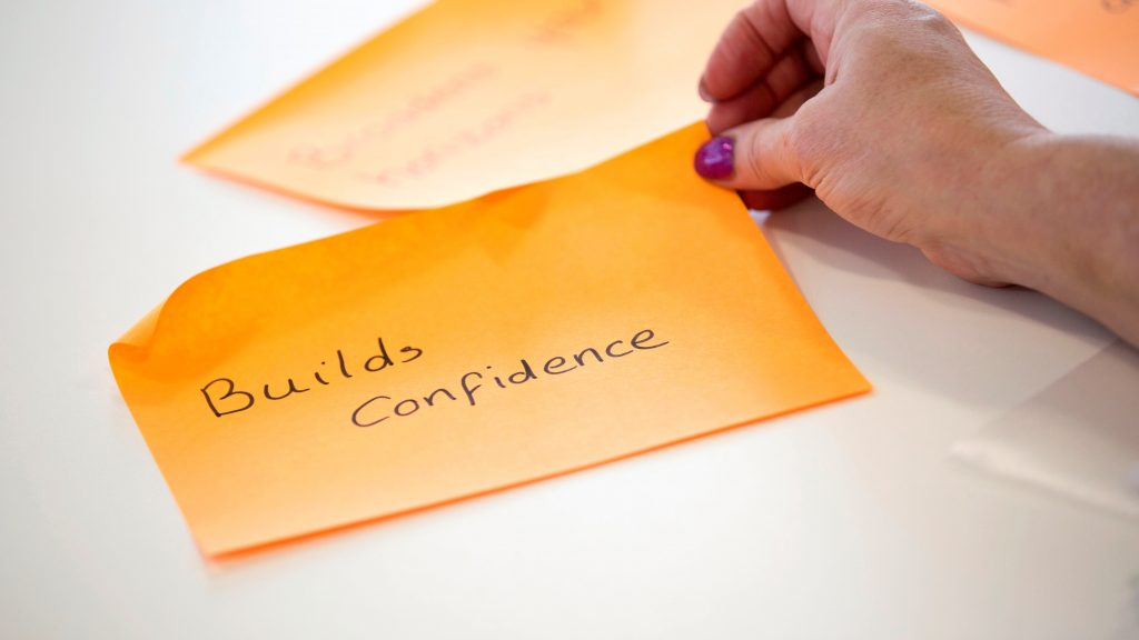 Hand holding a Post-It note with text 'Builds Confidence'