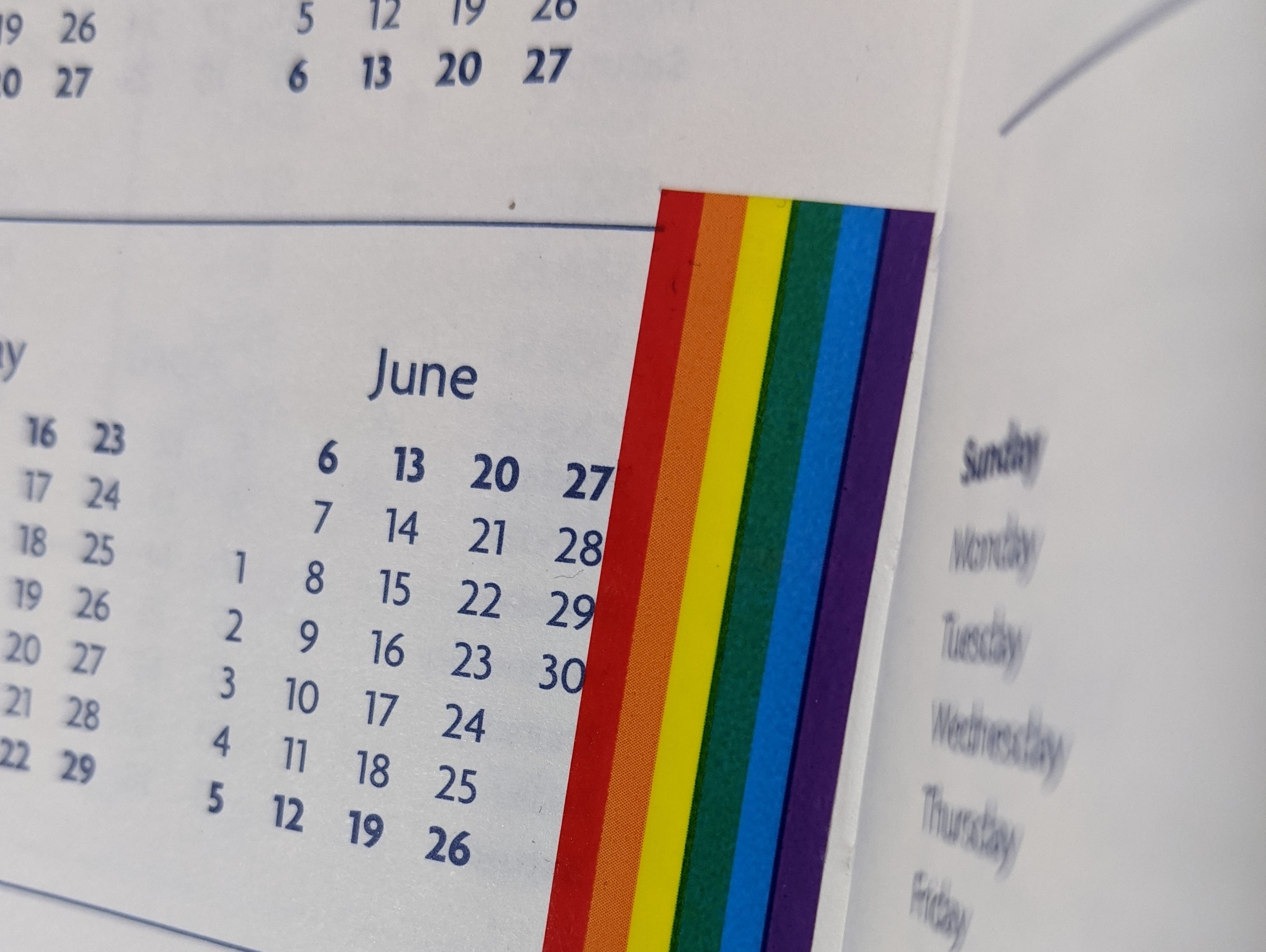 calendar showing the month of June, and a strip of rainbow tape