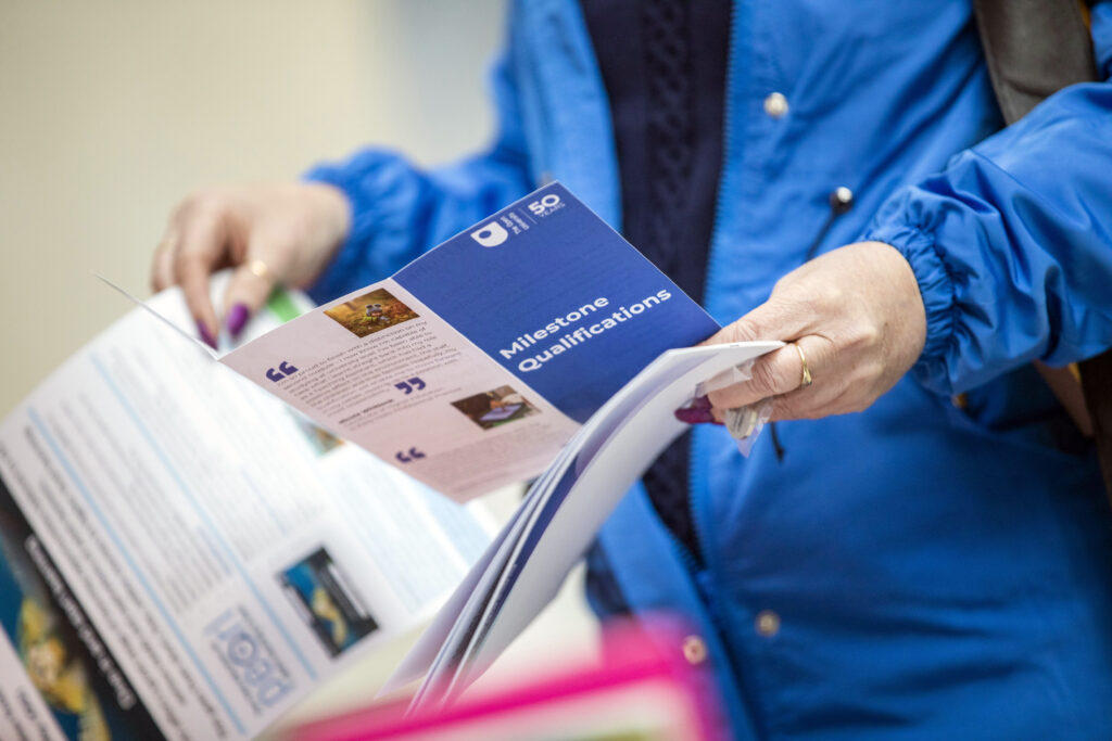 person holding a leaflet with text 'Milestone Qualifications'
