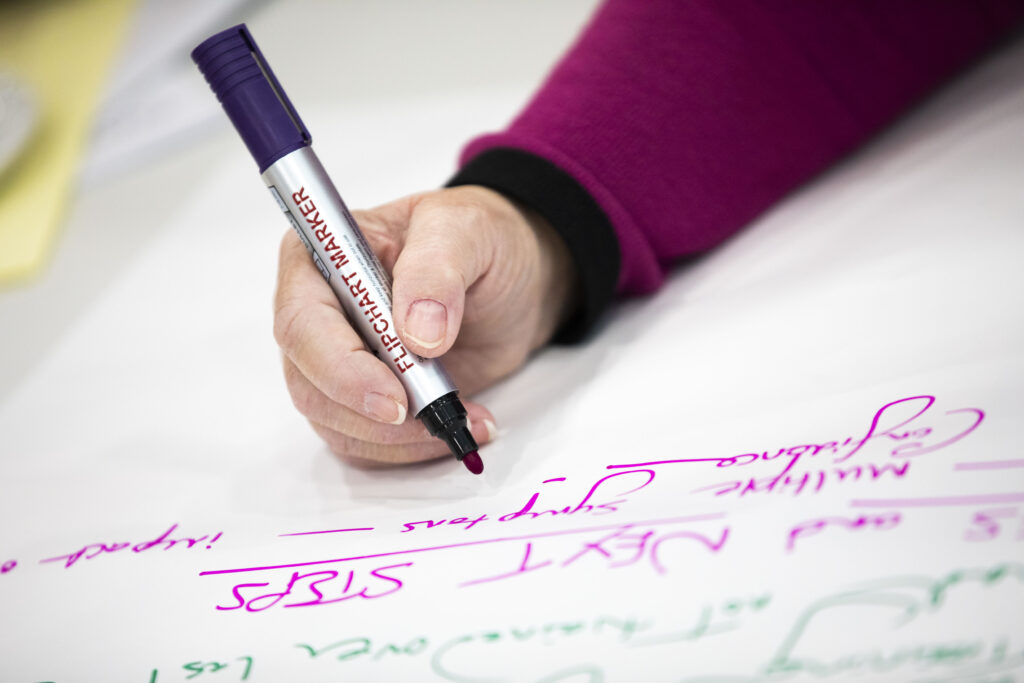 A person holds a pen which has just written 'Next Steps'